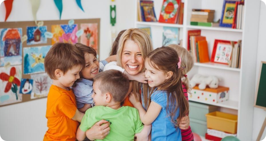 przedszkolaki obejmujące uśmiechniętą opiekunkę